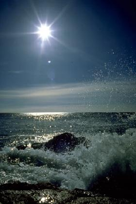 Starburst Sun Over Ocean, Splashing Shoreline Rocks